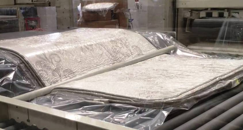 A compressed mattress being folded before roll packing